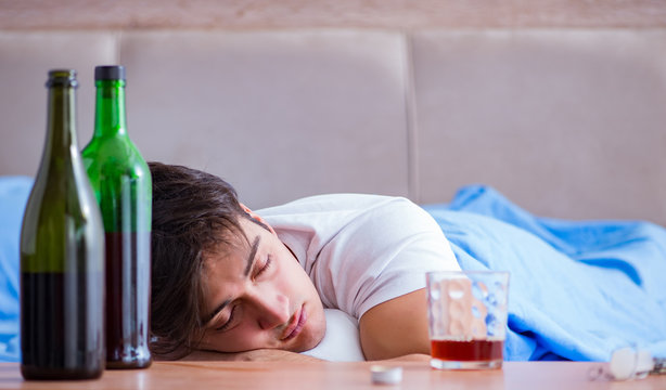 Man alcoholic drinking in bed going through break up depression