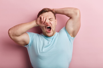 Sleepy young muscular strong man yawning, he rubs his eye in the morning, close up portrait, isolated pink background. lifestyle, free time, spare time