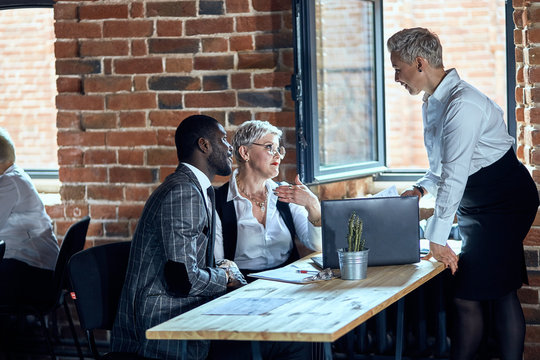 Two caucasian blonde adult women wear white office shirts work at table on laptop and one african adult man. Window open