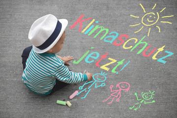 kleiner Junge malt mit Kreide - Klimaschutz