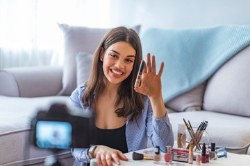 Happy smiling woman or beauty blogger with bronzer, brush and camera recording tutorial video at home.