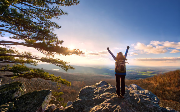 Female Hiker Raising Arms to the sun setting over a beautiful vista at the top of an Appalachian  mountain