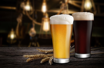 Glasses of Light Beer and Dark Beer with wheat on the bar counter in the restaurant at night, with copy space