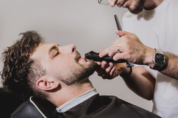 Spoed Foto op Canvas Kapsalon Young man with trendy haircut at barber shop. Barber does the hairstyle and beard trim.