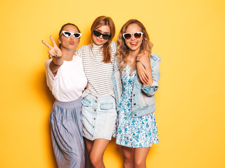 Three young beautiful smiling hipster girls in trendy summer clothes. Sexy carefree women posing near yellow wall in studio. Positive models going crazy and having fun in sunglasses Wall mural