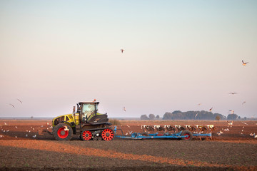 farmer with tractor plows field in late summer on countryside of lower saxony in germany