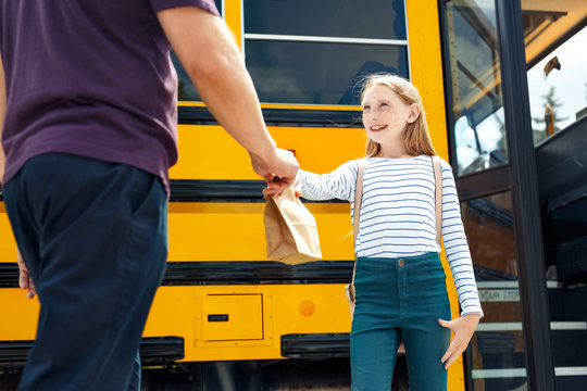 Father giving lunch bag to happy daughter going to school by bus close-up