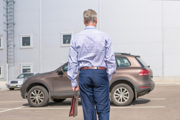 Middle-aged  tall gray-haired businessman in blue suit with brown briefcase walks to his car on the private parking