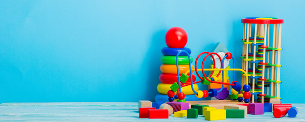 Baby toys on wooden table. Child development concept. Copy srace for text.