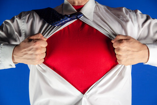 Businessman tearing off his suit on blue background, man pushes shirt with red t-shirt. Superhero.