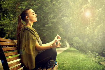 Young attractive female meditate in park. young woman resting in the lotus position in the park after a hard day. Wall mural