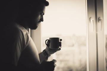 bearded man by the window