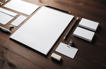 Photo of blank corporate stationery set on wood table background. Template for branding design.