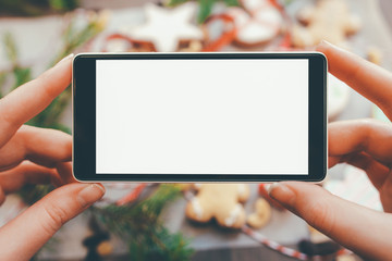 Festive culinary blog. Closeup of lady hands holding smartphone with white mockup screen over handmade gingerbread cookies.