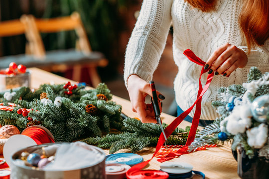 Craft workshop. Cropped shot of female florist using red ribbon, green fir tree twig to create Christmas interior decoration.
