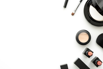 Flat lay image of beauty cosmetics make up with lipsticks, concealer, foundation powder and brush on white background. Top view with copy space, for your text.