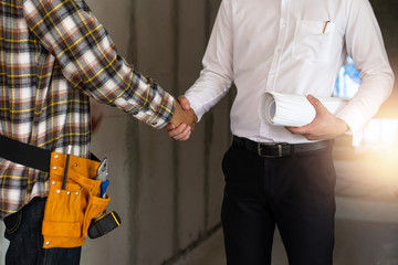 Close up engineer shaking  hand with building contractor in construction site , successful negotiate of manager and industrial agreement cooperation concept