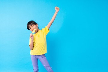 young girl eating ice cream stick on blue background in studio