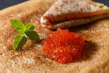 Stack of pancakes with red caviar on dark rustic background, close up