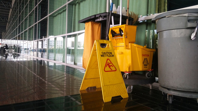 The warning signs cleaning and caution wet floor in the building and janitorial car.