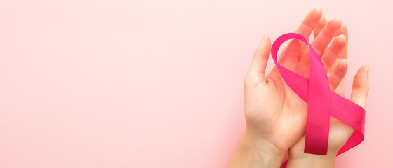 Breast cancer awareness month horizontal banner with copy space. Woman's hand holding pink ribbon over pink background. Healthcare and medicine concept.