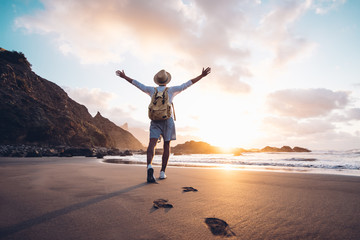 Young man arms outstretched by the sea at sunrise enjoying freedom and life, people travel wellbeing concept Fotomurales