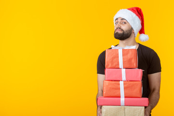 Disgruntled young man with a beard in a Santa Claus hat holds five gift boxes posing on a yellow background with copyspace. Concept of gifts and greetings for Christmas and New Year.
