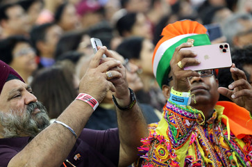 """People take photos with their mobile phones as they participate in the """"Howdy Modi"""" event in Houston"""