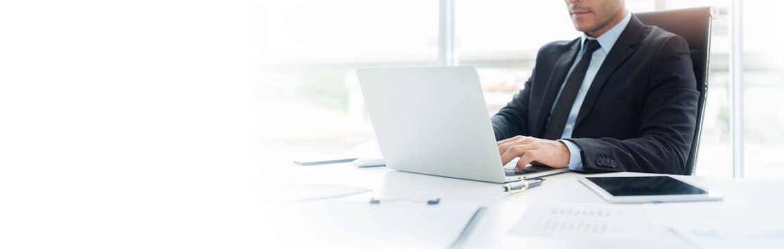 Concentrated Businessman is working on Laptop computer.