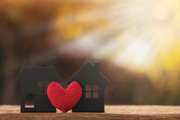 The buying a new real estate as a gift to family or the one loved concept, a home model and red heart put on the old wood on sunlight in the public park.
