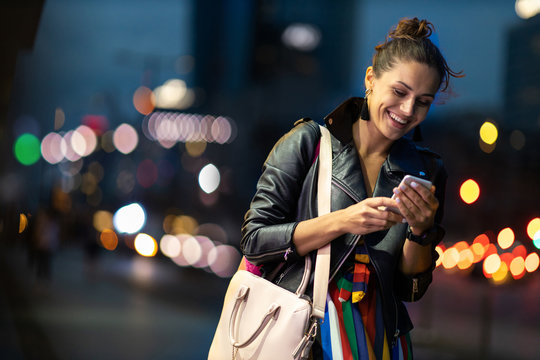 Young woman with smartphone at night in a urban city area