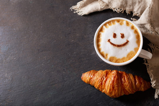 cup of cappuccino coffee with drawing smile on milk foam and croissant