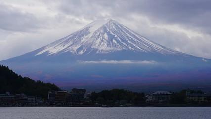 Wall Mural - 4K Time lapse of mount Fuji in sunrise from lake Kawaguchiko. Beautiful cloudscape over Fuji. Mount Fuji or Fuji san is the most famous natural landmark in Japan. Fuji view from lake Kawaguchiko.