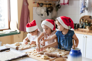 Kids are cooking Christmas cookies in cozy kitchen. Sisters prepare holiday food for family together. Cute girls bake homemade festive biscuits. Lifestyle moment. Santa helpers. Children chef concept