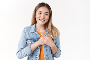 You in my heart. Tender caring cute asian young girl blond hairstyle hold hands chest pleased grateful wonderful memories warmth cherish romantic moments smiling delighted look lovely camera