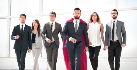 businessman in a red superhero cloak and his business team