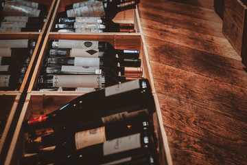 Luxury wine stock in private boutique, big selection of red wine are kept in wooden boxes.