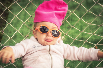 Happy child with funny face in eyeglasses having fun on hammock carefree childhood lifestyle