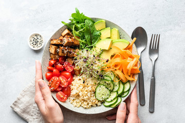 Buddha bowl salad in female hands, balanced meal. Bright grey concrete background, table top view. Weight loss, dieting concept