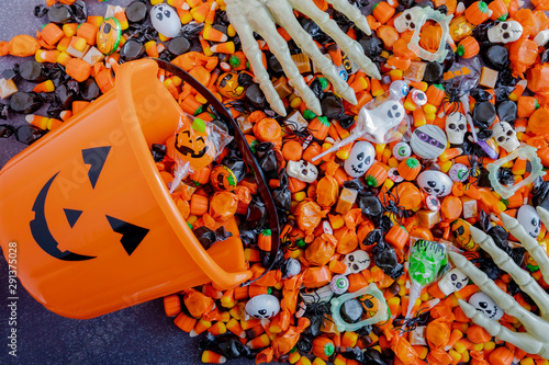 Halloween candy spilling out of orange pumpkin bucket