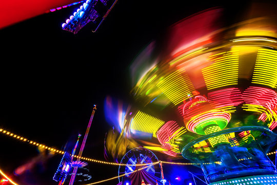 Abstract colorful funfair carosuell in neon colors in motion at a fun fair