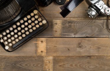 Vintage retro typewriter and analog film camera on wooden table background top view flat lay from above - journalism or writer concept with copy space