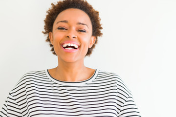 Beautiful young african american woman smiling confident to the camera showing teeth over isolated white background Wall mural