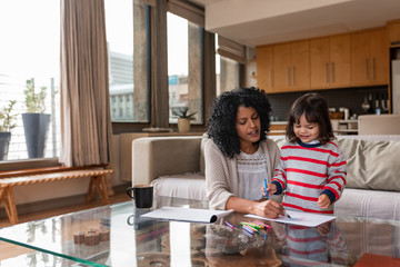 Caring mother and her little girl coloring together at home