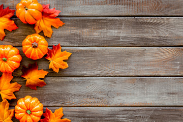 Autumn background with leaves and pumpkins on dark wooden top view space for text frame