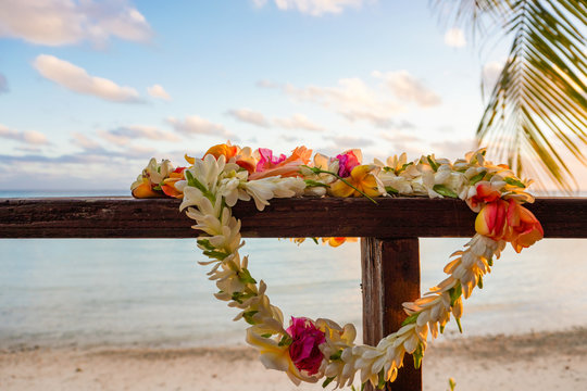A beautiful lei of flowers rests on a the railing of a wooden deck overlooking a lagoon in French Polynesia in the South Pacific