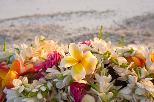 A lei of beautiful tropical flowers rests on a railing above a white sandy beach