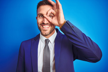 Close up picture of young handsome business man over blue isolated background doing ok gesture with hand smiling, eye looking through fingers with happy face.