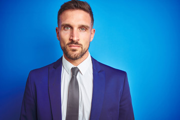 Close up picture of young handsome business man over blue isolated background with serious expression on face. Simple and natural looking at the camera.