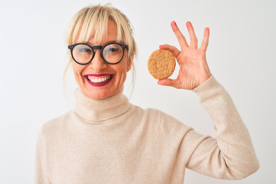 Middle age woman wearing glasses holding cookie standing over isolated white background with a happy face standing and smiling with a confident smile showing teeth